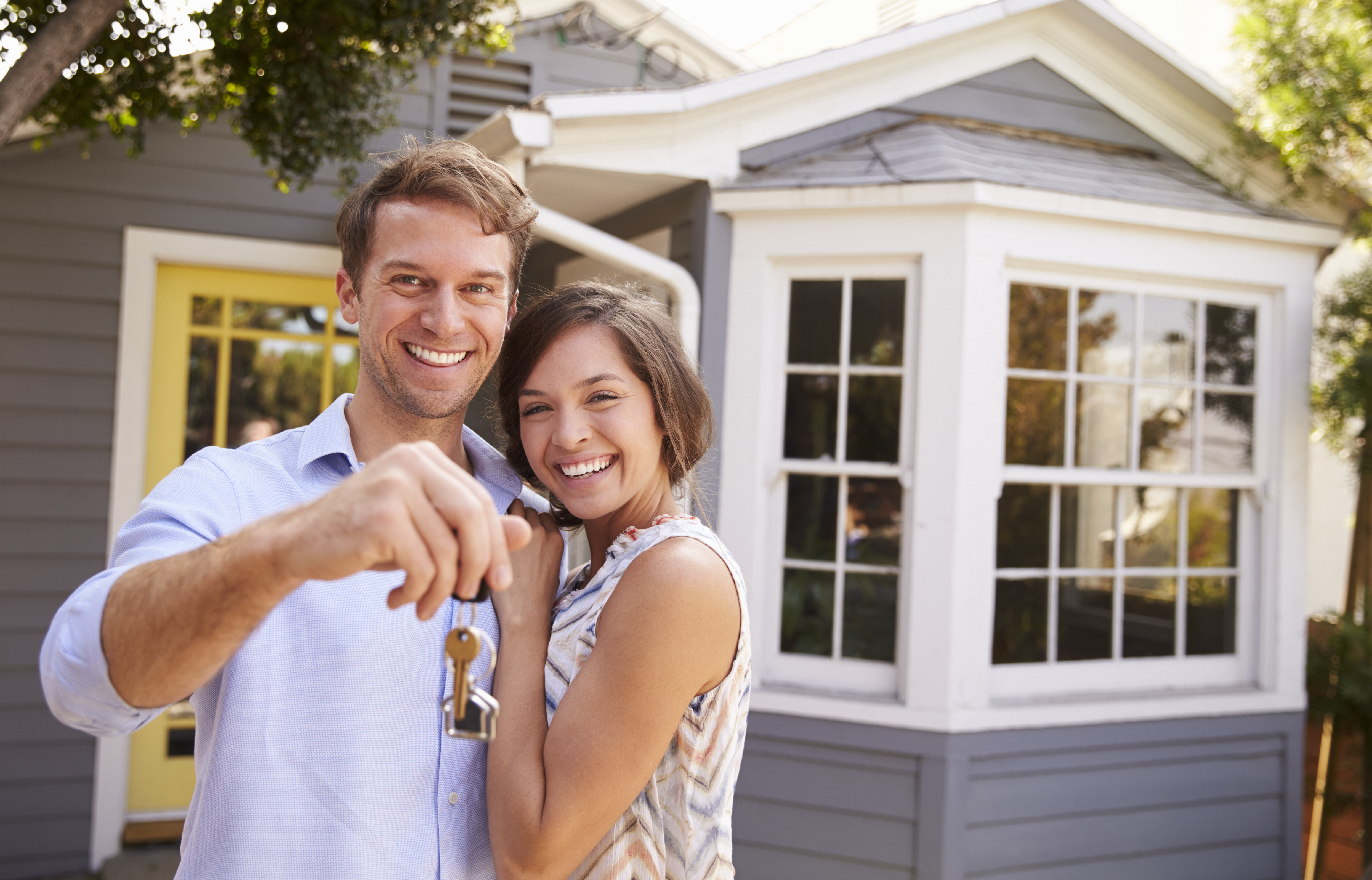 A young happy couple holding out keys while standing in front of their new home