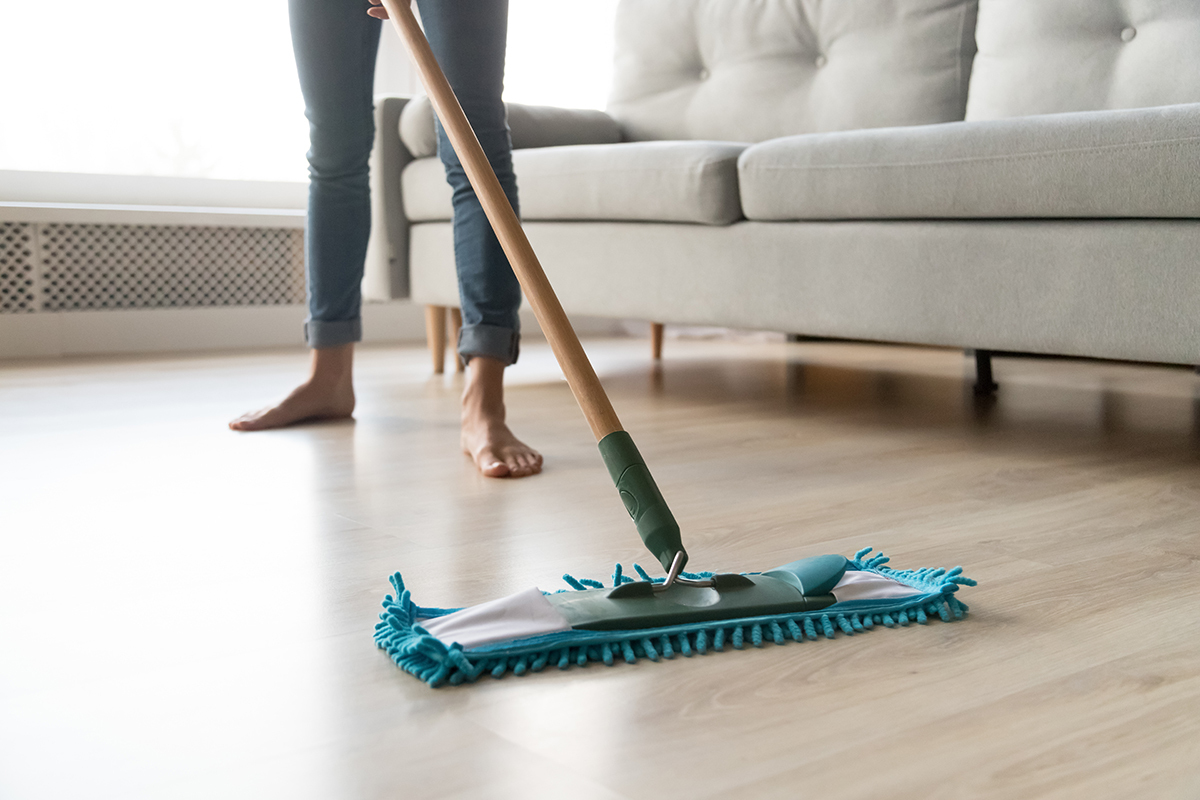 Woman housewife wash wooden laminate floor in modern living room, female cleaner housekeeper maid holding mop cleaning at home, domestic housework professional household service concept close up view